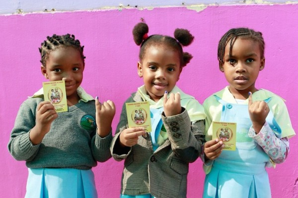 Girls in Mozambique show off their Shot@Life immunization cards for World Immunization Week