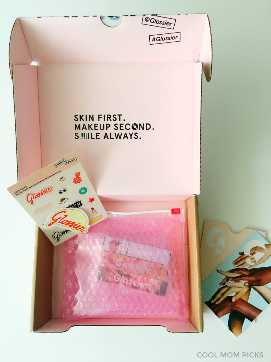 Glossier orders come in a fun box with some free samples and stickers, making it a great gift