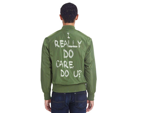 I Really Do Care Do U bomber jacket, with 100% of the proceeds supporting RAICES #keepfamiliestogether