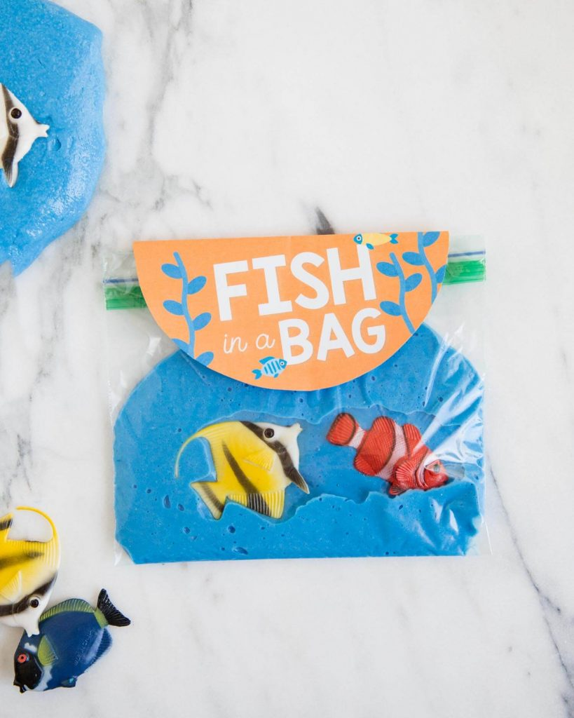 Clever goodie bag favor for a slime party: Seal it up in a baggie and tuck in a few free fish printables from Jamielyn at I Heart Naptime