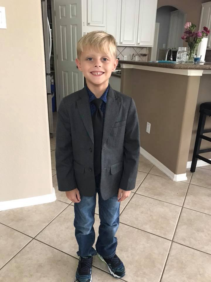 Noah Speck in his coat and tie for school, before Michael Strahan's act of kindness