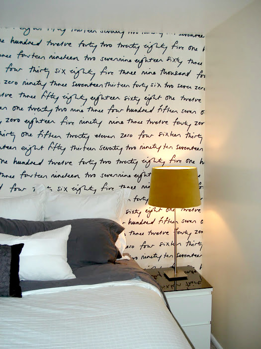 How to hang fabric instead of wallpaper: Graphic fabric behind a bed at Numbered Street Designs blog